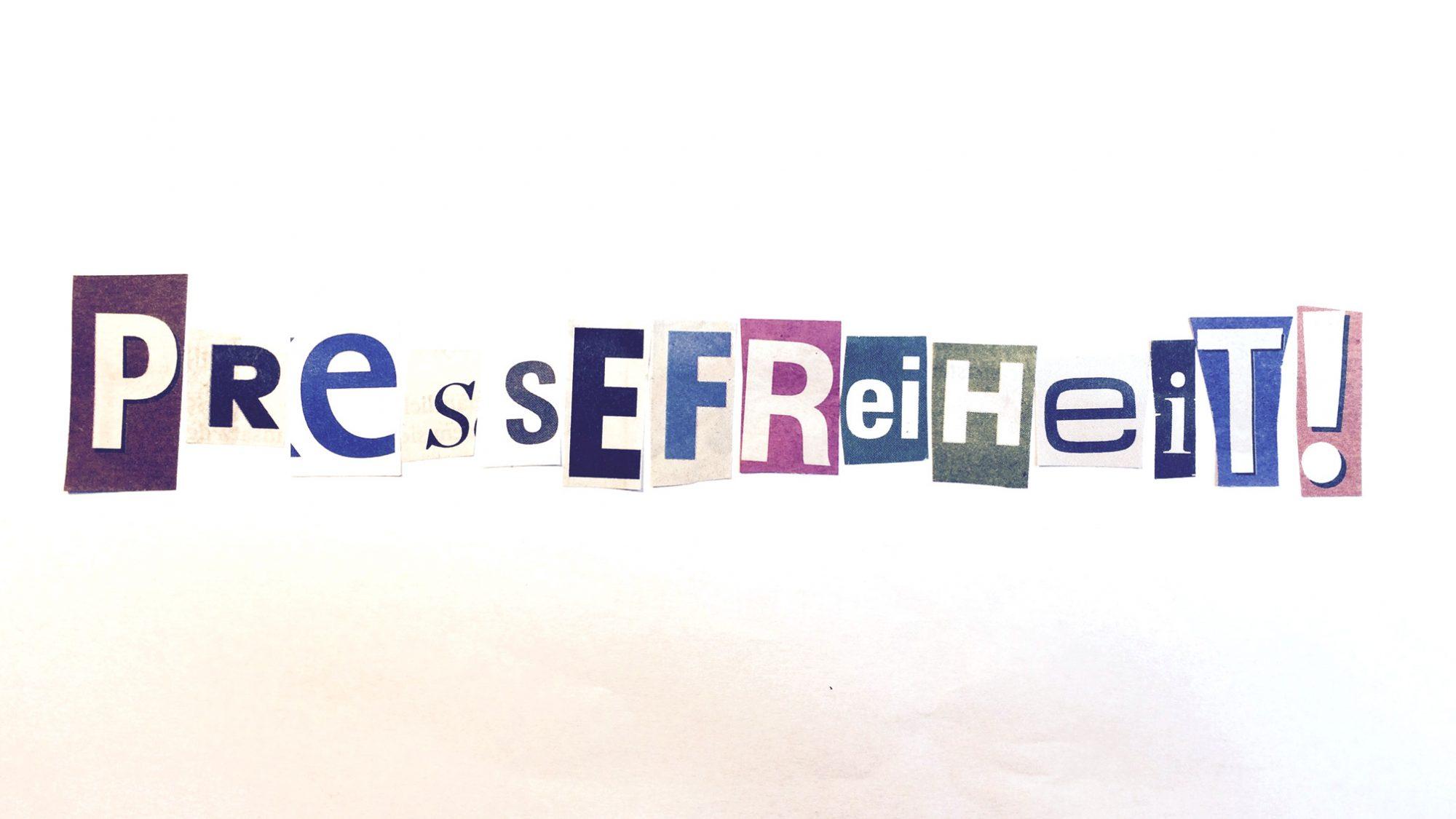 Das Wort Pressefreiheit zusammengesetzt aus einzelnen ausgeschnittenen Zeitungsbuchstaben.